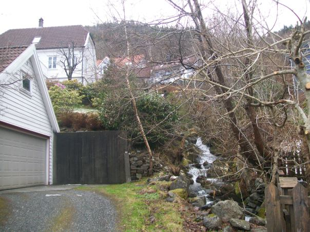 Waterfall runs between houses.