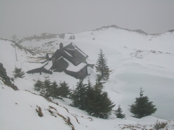 Cloud clears to reveal a cabin in 'Christmas Card' setting.
